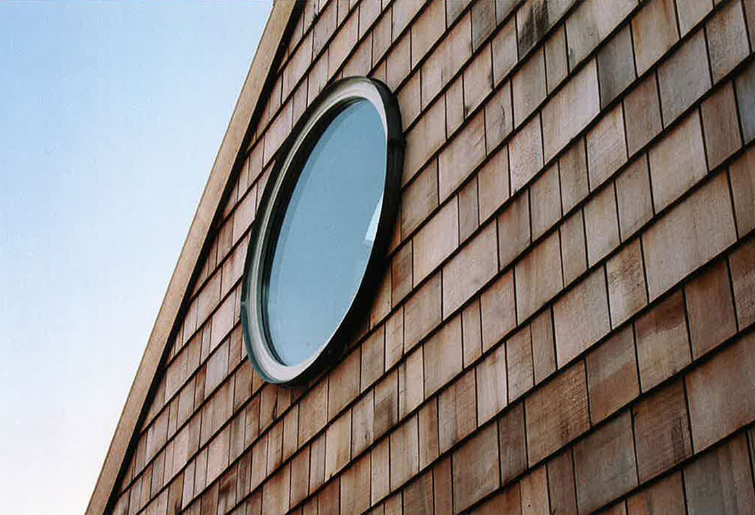 Holzfassade mit Schindeln und modernem Bullauge
