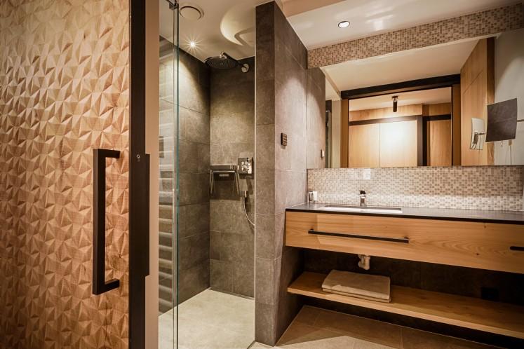 Thema Sinnlichkeit: fühlbare Oberflächen. Aufwendige dreidimensionale Fräsungen im Holz, matter Stein, glatte Fliesen. Hotel Peternhof****s, Wohlfühlresort im Kaiserwinkel