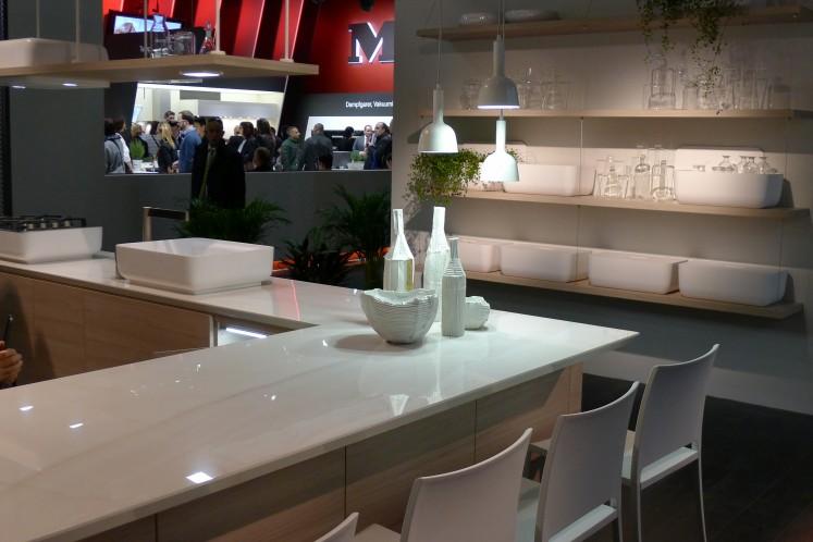 Dass Sitzen am Küchenblock auch ohne Barhocker realisierbar ist, zeigt dieser Hersteller - aufgesetzte Spülen und Kochplatten machen es möglich.